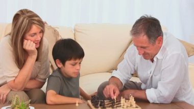 A boy playing chess with his grandfather — Vídeo Stock