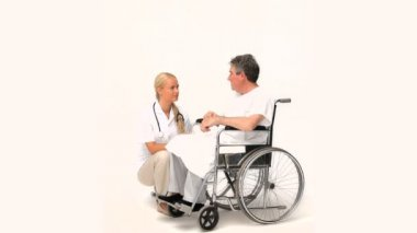 Man in a wheelchair talking to his nurse — Stock Video