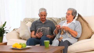Mulher de tricô enquanto seu marido está lendo — Vídeo Stock