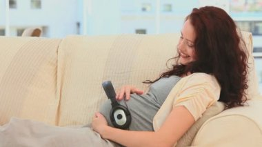 Pregnant woman with headphones on her belly — Stock Video