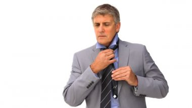 A class businessman putting on his tie against a white background