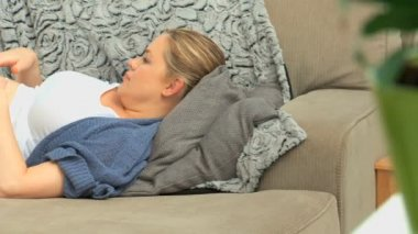 Expecting woman massaging her belly on her sofa