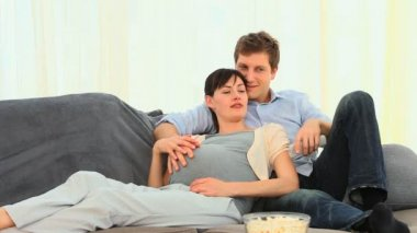 Man stroking the belly of his pregnant wife in the couch