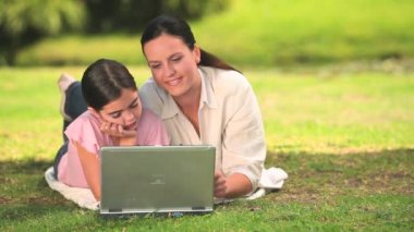 Woman and daughter using a laptop outdoors — Stock Video