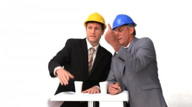 Twee architecten met veiligheidshelmen spreken — Stockvideo