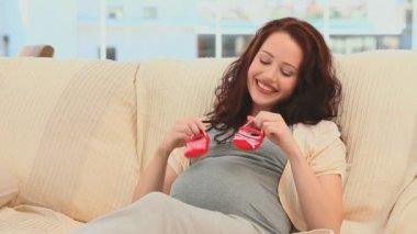 Pregnant woman playing with baby shoes on the sofa — Stock Video #15556803
