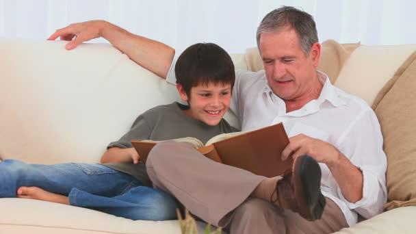 Un niño mirando un álbum — Vídeo de stock