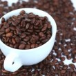 Cup filled with coffee beans turning on a bed of coffee beans — Stock Video