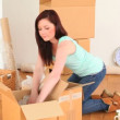 Cute brunette emptying cardboards in her new flat - Stock Photo