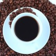 Cup of coffee surrounded by coffee beans turning - Stock Photo