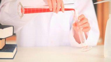 Cientista fêmea derramando um líquido vermelho de um copo para outro — Vídeo Stock