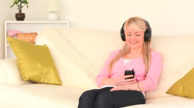 Blond-haired woman listening to music with headphones — Stock Video