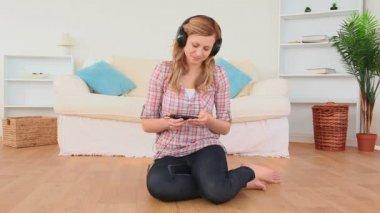 Glückliche blonden Frau, die Musik zu Hause hören — Stockvideo