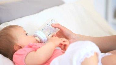 Söt baby matas på sängen — Stockvideo