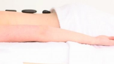 Good looking woman having some pebbles on her back while lying on a towel — Stock Video