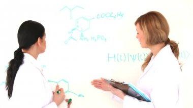 Mulheres de cientista escrevendo uma fórmula — Vídeo Stock