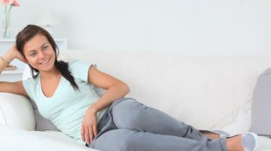 Young attractive woman having a rest while lying on a sofa in the living room — Stock Video
