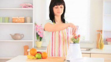 Dark-haired woman preparing a smoothie — Stock Video