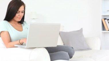 若いブルネットの女性のソファに座って彼女のラップトップでリラックス — ストックビデオ