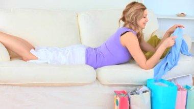 молодая женщина, лежа на диване в восторге от ее покупки — Стоковое видео