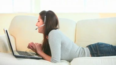Woman phoning on sofa with laptop and headphones — Stock Video