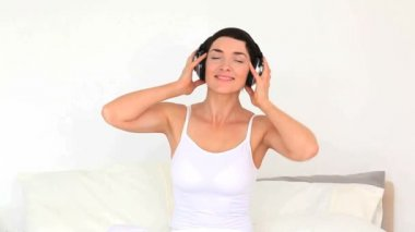 Brunette woman listening music with headphones sitting on a bed — Stock Video