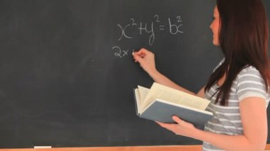 Beautiful woman writing a mathematical formula on a blackboard — Stock Video
