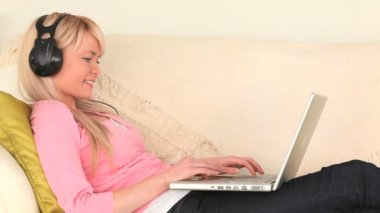 Attractive woman listening to music and surfing on her laptop — Stock Video