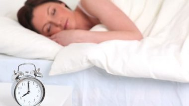 Alarm clock ringing while a cute woman is sleeping — Stock Video