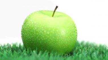 Green apple on grass rotating — Stock Video