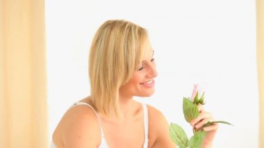 Blond-haired woman smelling a rose — Stock Video