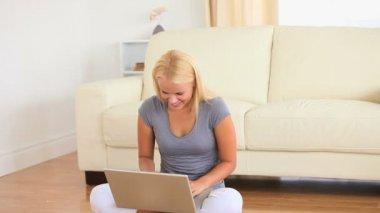 女子坐在地板上用笔记本在她的大腿上 — 图库视频影像