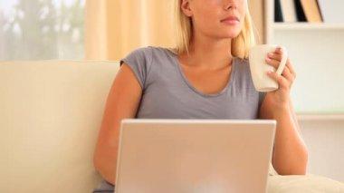 žena myšlení s ní notebook na klíně, zatímco držíte šálek kávy sedí na pohovce — Stock video
