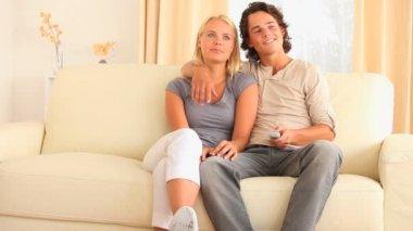 Wesoły para siedzi na kanapie oglądając tv — Wideo stockowe