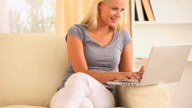 Kobieta wyleguje się na kanapie, wyszukiwanie w internecie — Wideo stockowe