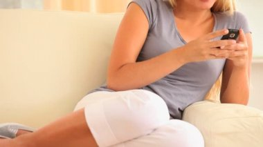 Cheerful woman sitting on a sofa texting with a mobile — Stock Video