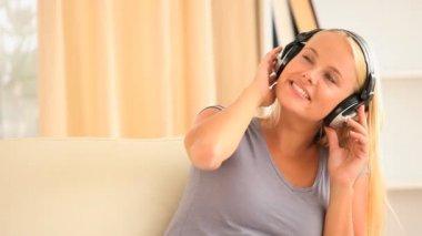 音楽を聴くソファに座っている女性 — ストックビデオ