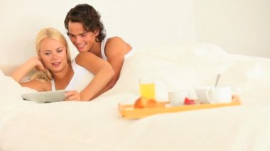 Happy couple together in bed with breakfast and tablet — Stock Video