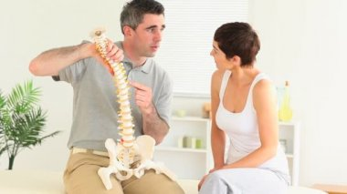 Chiropractor explaining the spine to a woman — Stock Video