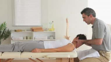 Chiropractor examining a woman's neck — Stock Video
