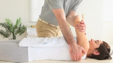 Chiropractor stretching the shoulder of a woman — Stock Video