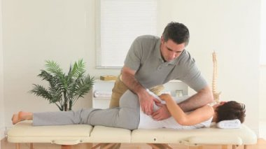 Chiropractor stretching the back of a woman — Stock Video