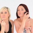 Well-dressed young women applying make-up — Stock Video #20304537