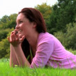 Lying woman telephoning on lawn — Video