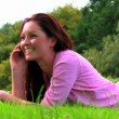 Lying woman with mobile phone on lawn — Vídeo Stock