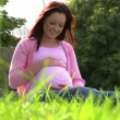 Pregnant woman sitting on lawn touching her belly — Stock Video