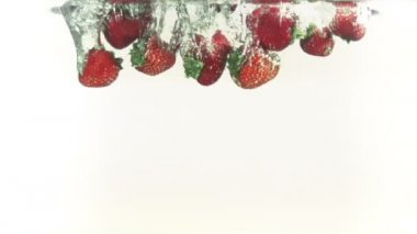 Strawberries splashing into water in super slow motion — Stock Video