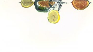 Slices of oranges, limes and lemons falling into water in super slow motion — Stock Video