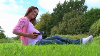 Pregnant woman sitting on lawn — Stock Video #20304769