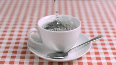 Water poured in super slow motion in a cup with tea — Stock Video